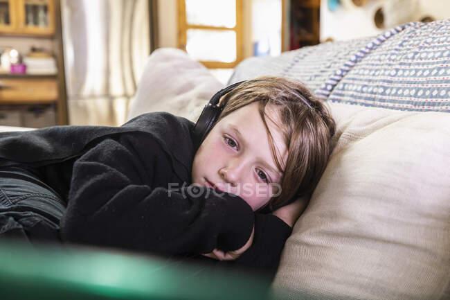 Jovem deitado no sofá olhando para o computador portátil — Fotografia de Stock