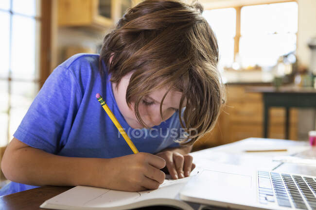 Young boy at home writing and drawing in his drawing pad — Stock Photo