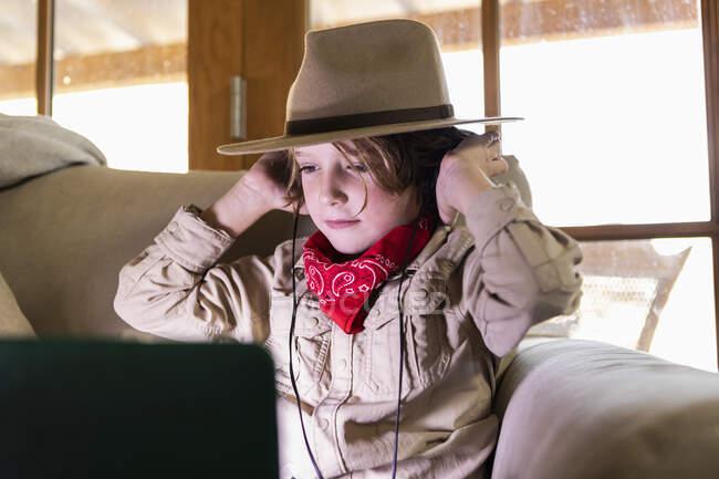 Мальчик в сафари и наушниках смотрит фильм на ноутбуке — стоковое фото