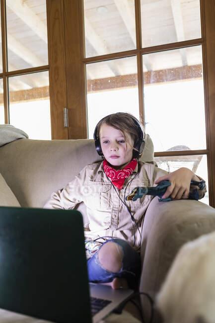 Молодий хлопчик у сафарі і навушники дивляться фільм на ноутбуку. — стокове фото