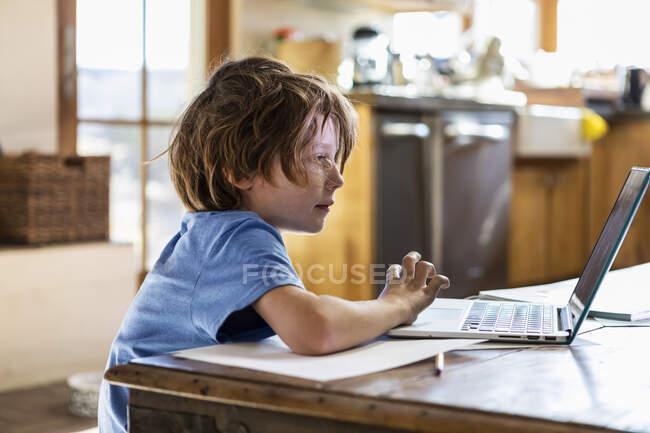 Niño usando su computadora portátil en casa - foto de stock