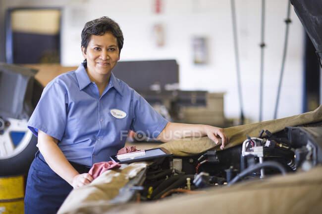 Retrato do mecânico hispânico feminino na oficina de reparação de automóveis — Fotografia de Stock
