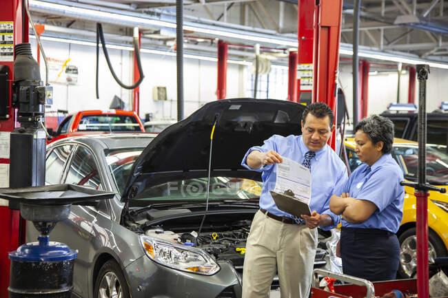 Proprietário da oficina de reparação de automóveis conversando com mecânico feminino hispânico — Fotografia de Stock