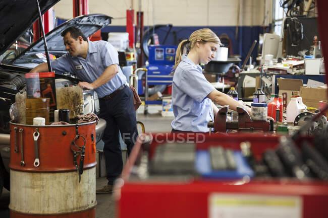 Mecânico feminino caucasiano trabalhando no motor na oficina de reparação de automóveis com colega de trabalho hispânico no fundo — Fotografia de Stock