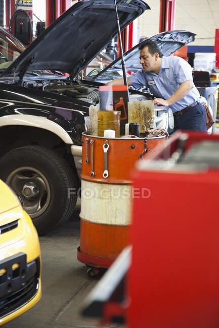 Латиноамериканец прислонился к двигателю автомобиля, над которым он работал в автомастерской — стоковое фото