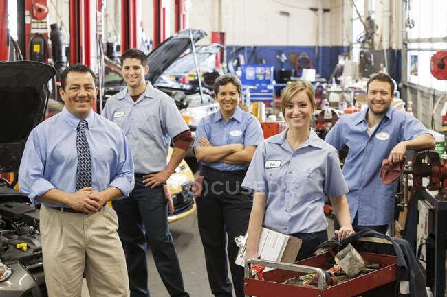 Retrato de sorrindo equipe oficina de reparação de automóveis com proprietário masculino hispânico — Fotografia de Stock