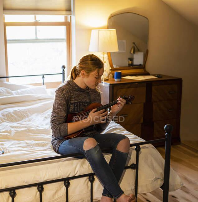 Adolescente tocando su violín en su dormitorio - foto de stock