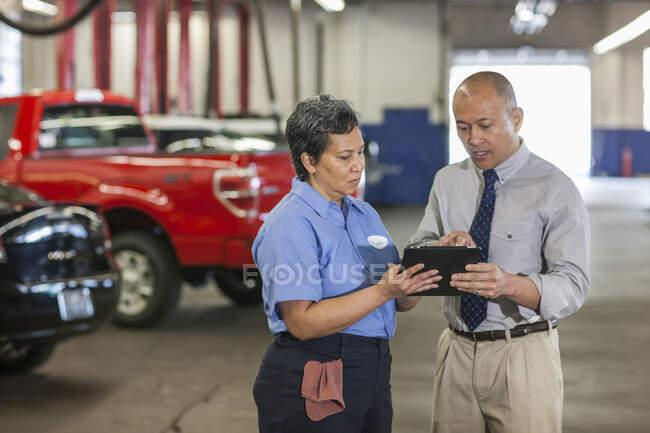Менеджер автомастерской Пасифик Айлендер разговаривает с латиноамериканским механиком — стоковое фото