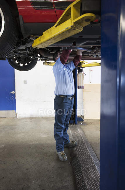 Mechanic in a repair shop working on the underside of a car up on a lift — Stock Photo
