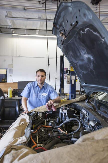Портрет улыбающегося кавказского механика в автомастерской — стоковое фото