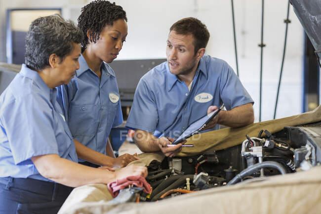 Três mecânicos compartilhando um tablet digital e planejando o trabalho em um carro para reparo — Fotografia de Stock