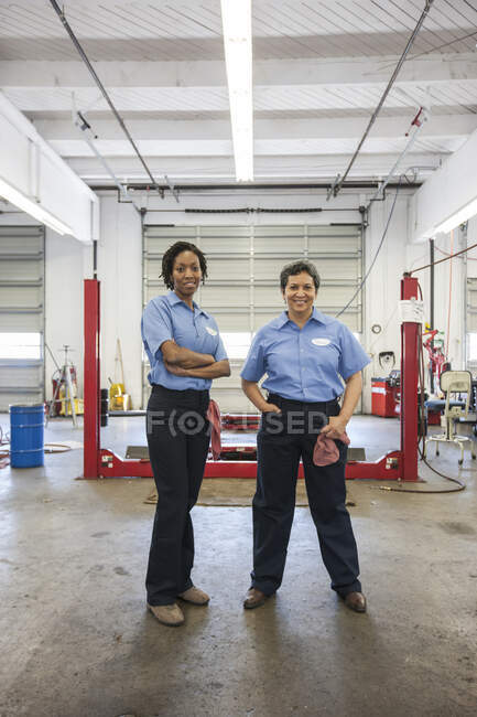 Retrato de dois sorridentes mecânica feminina em uma oficina de reparação automóvel. — Fotografia de Stock
