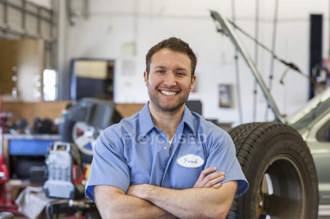 Retrato de um sorridente branco mecânico masculino em uma oficina de reparação de automóveis — Fotografia de Stock