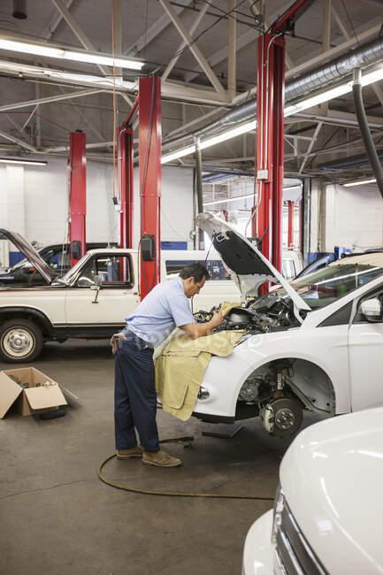 Латиноамериканський механік спирається на автомобіль, коли працює на відсіку двигуна в авторемонтній майстерні. — стокове фото
