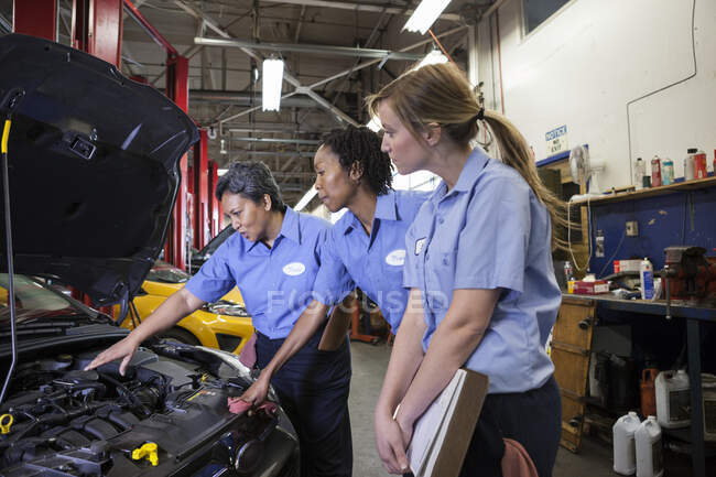 Three female mechanics talking as they looking inside the engine compartment of a car in a repair shop — Stock Photo