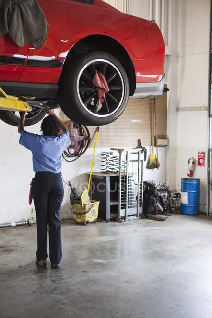 Механик в ремонтной мастерской, работающий на нижней стороне автомобиля на лифте — стоковое фото
