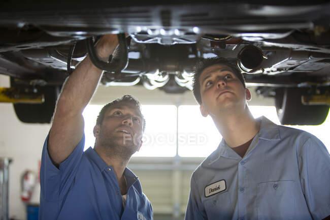 Dois mecânicos trabalhando na parte de baixo de um carro em um elevador em uma oficina de reparação — Fotografia de Stock