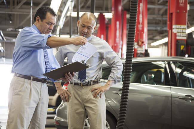 Мужчина, латиноамериканец, владелец автомастерской, разговаривает с менеджером компании Pacific Islander в магазине — стоковое фото