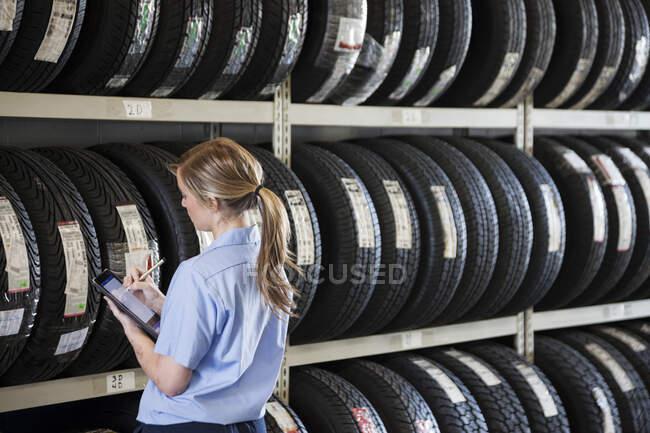 Молода жінка - механік інвентаризує нові шини в ремонтній майстерні. — стокове фото