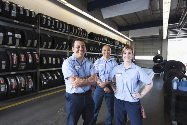 Portrait of smiling mechanics in auto repair shop, two men and a woman — Stock Photo