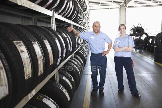 Retrato de homem sorridente e mecânico feminino por um rack de pneus em uma oficina — Fotografia de Stock