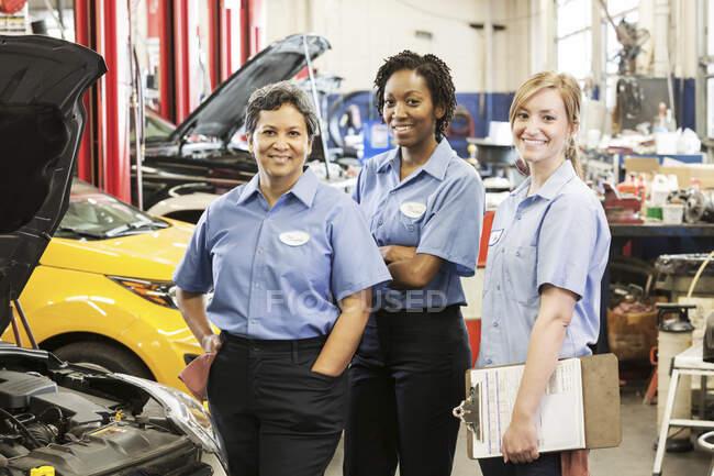 Retrato de três sorridentes mecânica feminina na oficina de reparação automóvel — Fotografia de Stock