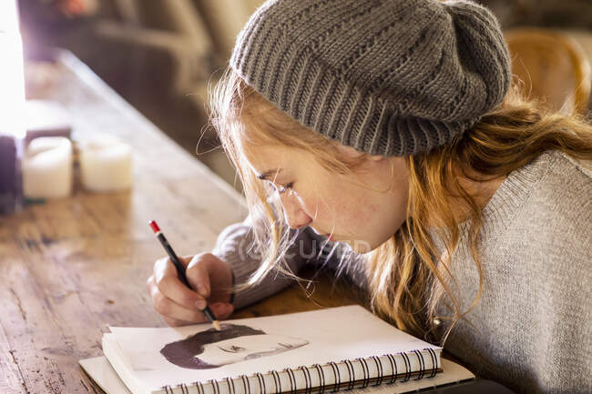 Teenage girl in a woolly hat drawing with a pencil on a sketchpad. — Stock Photo