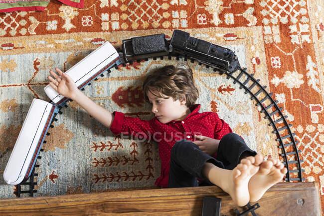 Над головою відкривається вид на хлопця, який грає зі своїм поїздом. — стокове фото