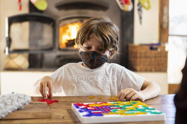 Giovane ragazzo indossando maschera gioco da tavolo a casa — Foto stock