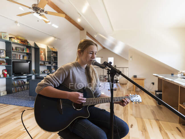 Fourteen year old teenage girl playing her guitar and singing at home in loft space — Stock Photo
