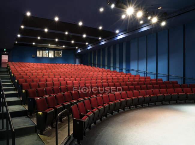 Empty auditorium, rows of raked seats. — Stock Photo