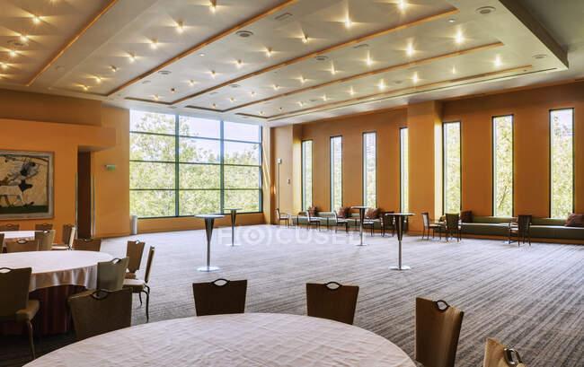 Grande quarto vazio em um hotel ou centro de conferências, mesas e cadeiras. — Fotografia de Stock