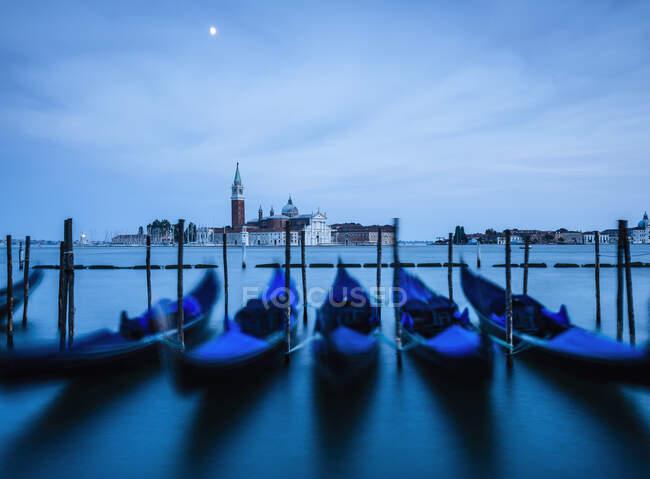 Venice lagoon, The Guideca viewed across the lagoon, gondolas moored, at night, moonlight. — Stock Photo