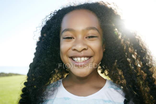Молода дівчина змішаної раси з довгим кучерявим чорним волоссям, посміхається до камери — стокове фото