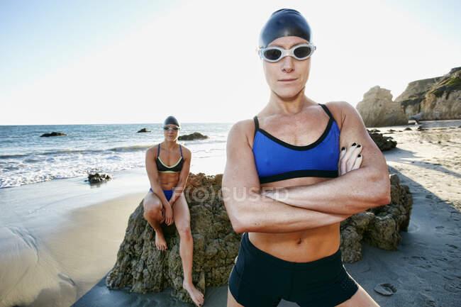 Dos hermanas, triatletas entrenando en trajes de baño, sombreros de baño y gafas. - foto de stock