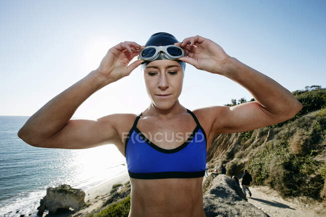 Young woman, triathlete in training in swimwear, swim hat and goggles on a beach. — Stock Photo