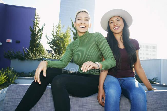 Dos mujeres jóvenes en una azotea posando para fotografías - foto de stock
