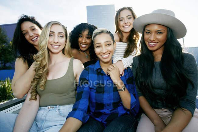 Groupe de jeunes femmes faisant la fête sur un toit de ville au crépuscule — Photo de stock