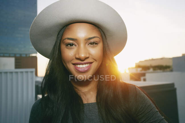Young woman smiling at camera on a city rooftop at dusk — Stock Photo