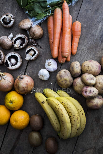 High angle close up of various fruits and vegetables on wooden table — Stock Photo