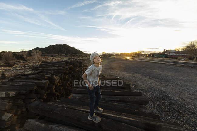 7 anos de idade menino de pé sozinho em laços ferroviários ao pôr do sol — Fotografia de Stock