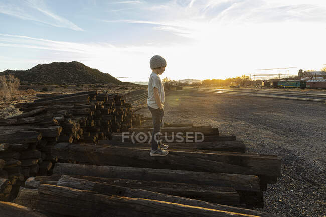 7 year old boy standing alone on railroad ties at sunset — Stock Photo