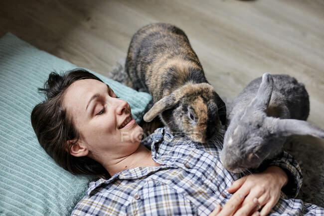 Mujer acostada en el suelo rodeada por dos conejos de casa de mascotas - foto de stock