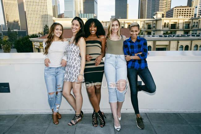 Cinq jeunes femmes posant pour des photos sur un toit, fond d'horizon de la ville — Photo de stock