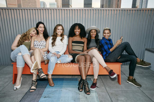 Group of young women partying on a city rooftop at dusk — Stock Photo