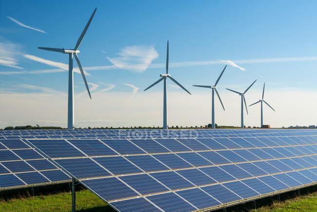 Wind turbine energy generators on wind farm, with solar panels underneath. — Stock Photo