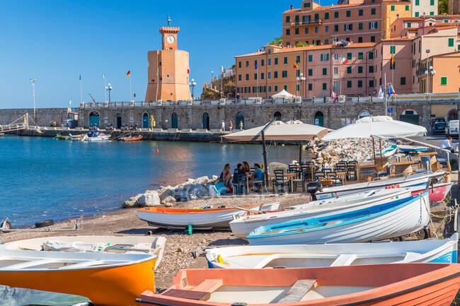 Puerto de Rio Marina, en la isla de Elba, edificios históricos adn barcos de pesca varados en el puerto. - foto de stock