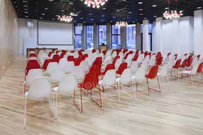 Велика порожня кімната з червоними і білими стільцями рядами, готові до презентації — стокове фото
