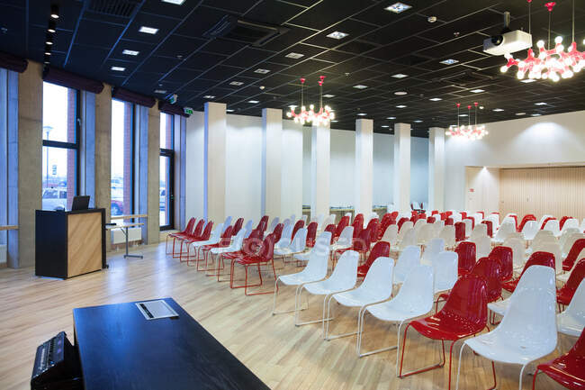Large empty room with red and white chairs in rows, ready for a presentation — Stock Photo