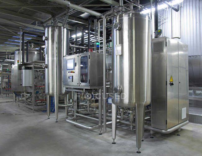 Beer brewing production plant. Large storage and fermenting tanks, stainless steel storage tanks and pipes. — Fotografia de Stock